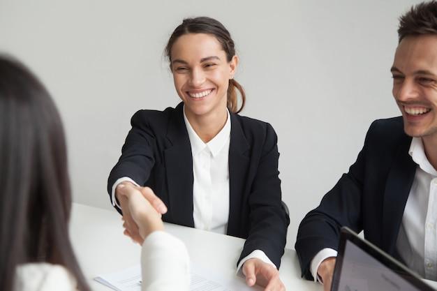 Lächelnde weibliche hr-händeschüttelngeschäftsfrau bei der gruppensitzung oder dem interview Kostenlose Fotos
