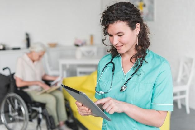 Lächelnde weibliche krankenschwester, die digitale tablette berührt Kostenlose Fotos