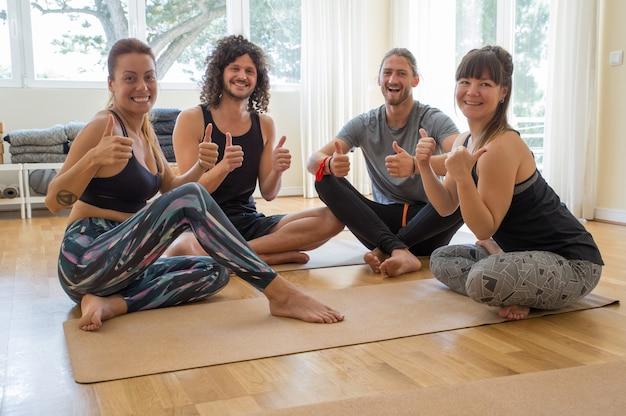 Lächelnde yogastudenten, die sich daumen zeigen Kostenlose Fotos