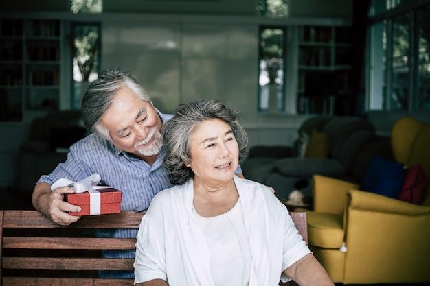 Lächelnder älterer ehemann, der die überraschung gibt seiner frau geschenkbox macht Kostenlose Fotos