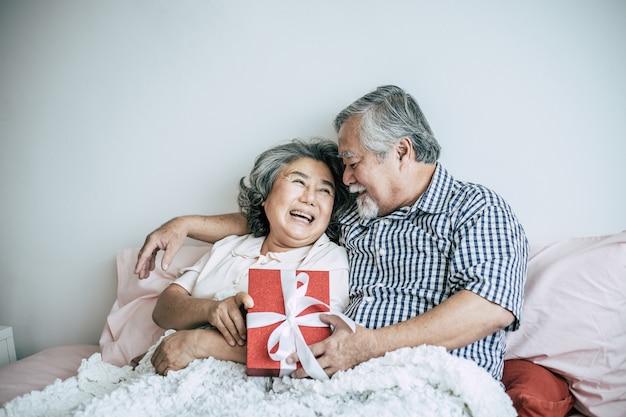 Lächelnder älterer ehemann, der die überraschung gibt seiner frau im schlafzimmer geschenkbox macht Kostenlose Fotos