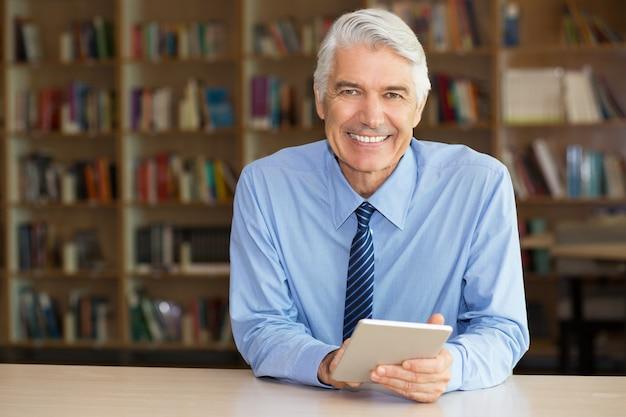 Lächelnder älterer geschäftsmann mit digitalen tablet Kostenlose Fotos