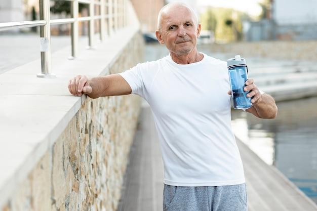 Lächelnder älterer mann, der beim kamerastillstehen schaut Kostenlose Fotos