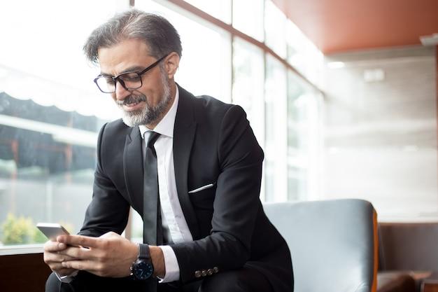 Lächelnder älterer mann, der nachricht auf telefon überprüft Kostenlose Fotos