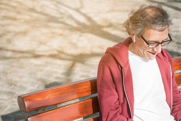 Lächelnder älterer mann mit drahtlosem kopfhörer auf seinem ohr, das auf bank sitzt Kostenlose Fotos
