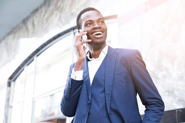 Lächelnder afrikanischer junger geschäftsmann, der am handy spricht Kostenlose Fotos