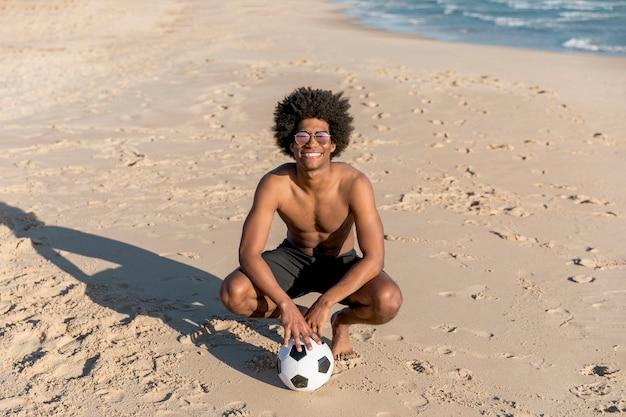 Lächelnder afroamerikanermann, der mit ball auf sommerstrand sitzt Kostenlose Fotos