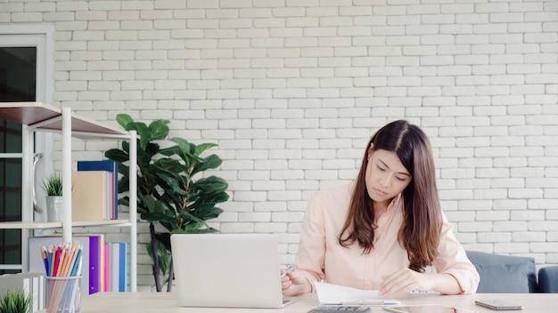 Lächelnder asiatischer frauenarbeitslaptop der schönen junge auf schreibtisch im wohnzimmer zu hause. Kostenlose Fotos