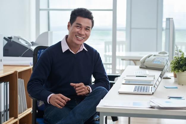 Lächelnder asiatischer mann, der am schreibtisch vor laptop im büro sitzt und kamera betrachtet Kostenlose Fotos