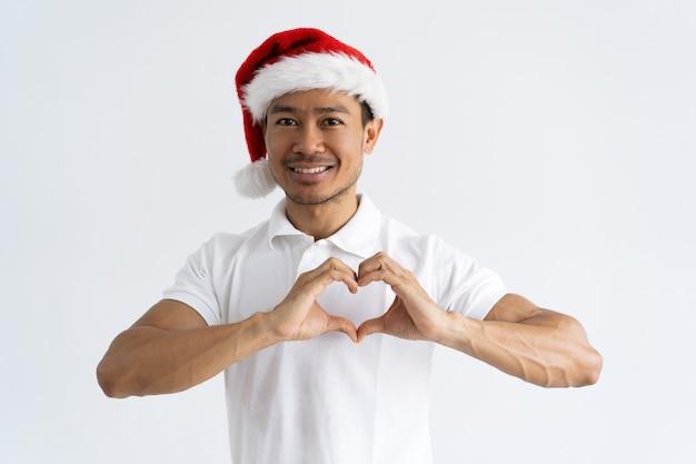 Lächelnder asiatischer mann, der herzgeste mit seinen händen macht Kostenlose Fotos