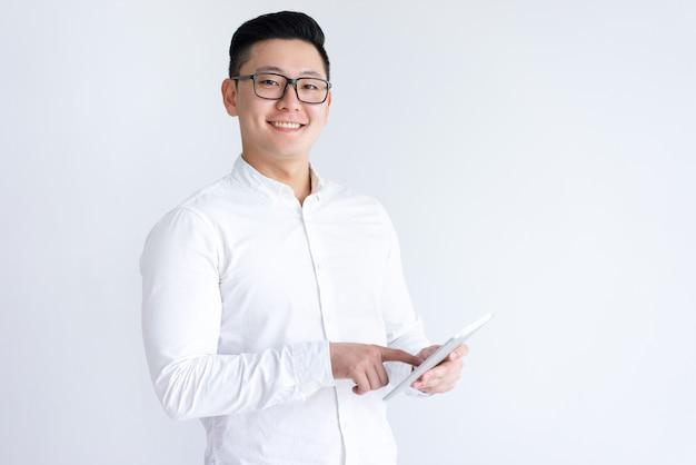 Lächelnder asiatischer mann, der tablet-computer verwendet Kostenlose Fotos