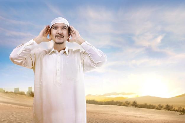 Lächelnder asiatischer moslemischer mann mit der kappe, die auf dem sand steht und betet Premium Fotos