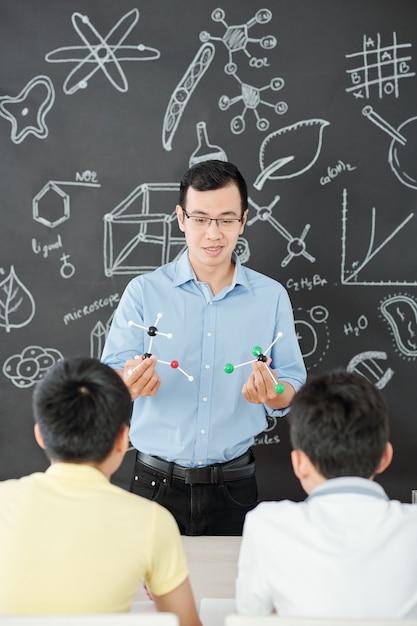 Lächelnder asiatischer naturwissenschaftslehrer, der neugierigen schulstürmen plastische molekülmodelle zeigt Premium Fotos