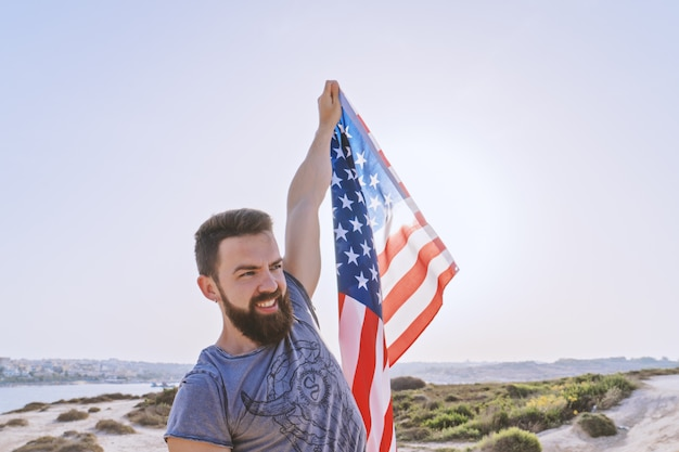 Lächelnder bärtiger mann, der in angehobener handamerikanische flagge hält Premium Fotos
