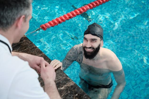 Lächelnder bärtiger schwimmer mit tätowierung, die im pool sitzt und trainer hört Premium Fotos