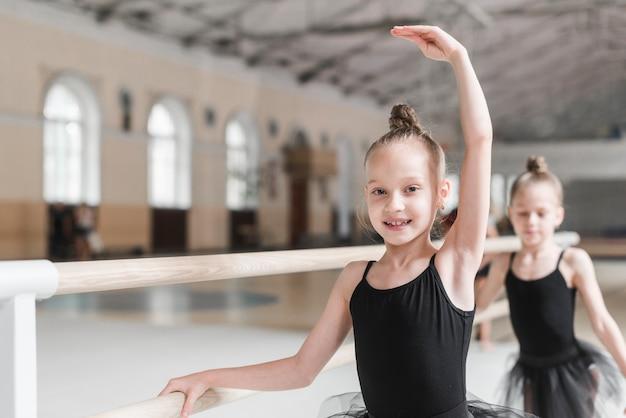 Lächelnder balletttänzer, der mit barre in der tanzklasse übt Kostenlose Fotos