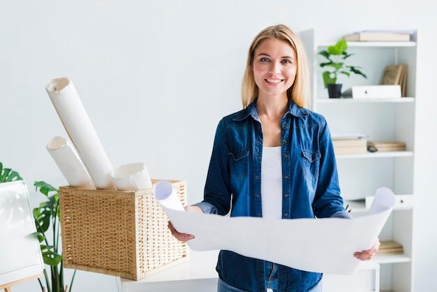 Lächelnder blonder frauendesigner mit großem ausgerolltem papierblatt Kostenlose Fotos