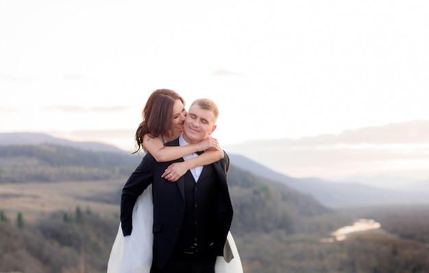 Lächelnder bräutigam hält braut auf dem rücken draußen mit hügeln auf dem hintergrund in der dämmerung Kostenlose Fotos