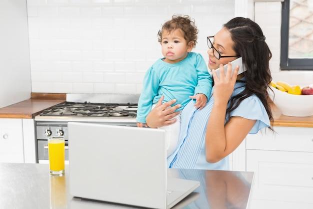Lächelnder brunette, der ihr baby hält und laptop beim telefonanruf in der küche verwendet Premium Fotos