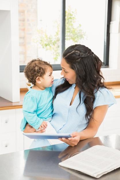 Lächelnder brunette, der ihr baby hält und tablette in der küche verwendet Premium Fotos