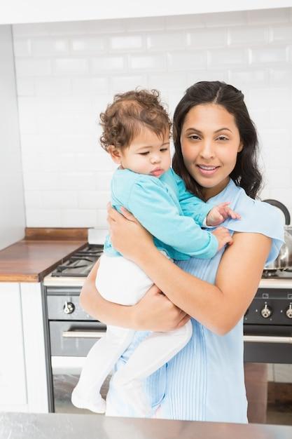 Lächelnder brunette, der ihr baby in der küche hält Premium Fotos