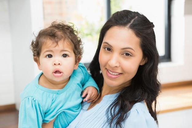 Lächelnder brunette, der zu hause ihr baby hält Premium Fotos