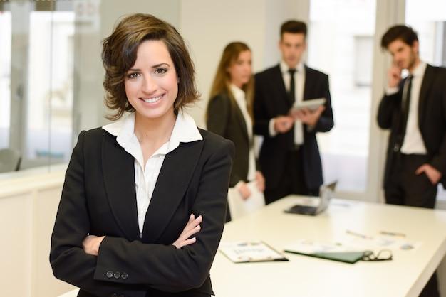 Lächelnder brunette manager mit verschränkten armen Kostenlose Fotos