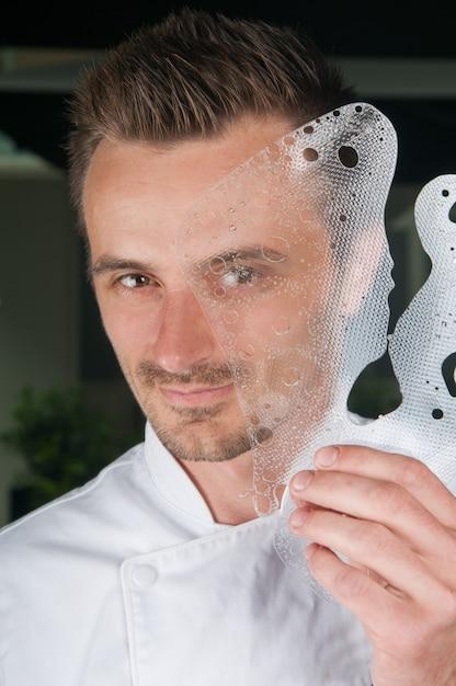 Lächelnder chef, der dekorative eisplatte vor seinem gesicht hält Kostenlose Fotos