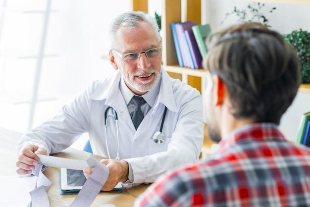 Lächelnder doktor, der auf patienten hört Kostenlose Fotos