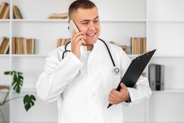 Lächelnder doktor, der ein klemmbrett hält und am telefon spricht Kostenlose Fotos