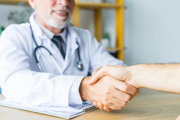 Lächelnder doktor, der hand des patienten rüttelt Kostenlose Fotos