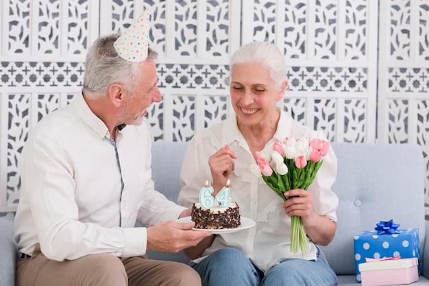 Lächelnder ehemann, der seiner frau tragenden partyhut geburtstagskuchen gibt Kostenlose Fotos