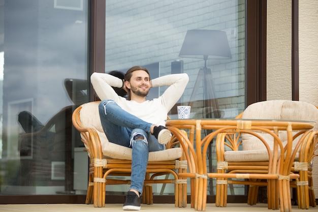 Lächelnder entspannter mann, der den angenehmen morgen sitzt auf der terrasse im freien genießt Kostenlose Fotos
