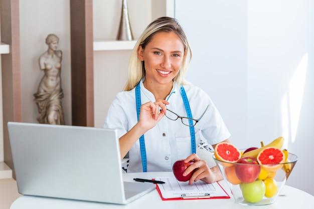 Lächelnder ernährungswissenschaftler im büro, das eine frucht hält Premium Fotos