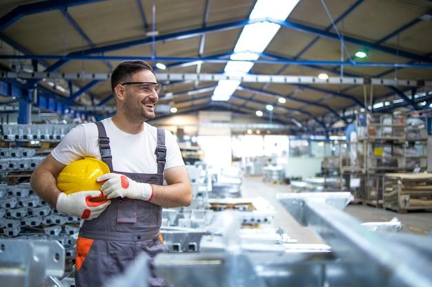 Lächelnder fabrikarbeiter mit schutzhelm, der in der fabrikproduktionslinie steht Kostenlose Fotos