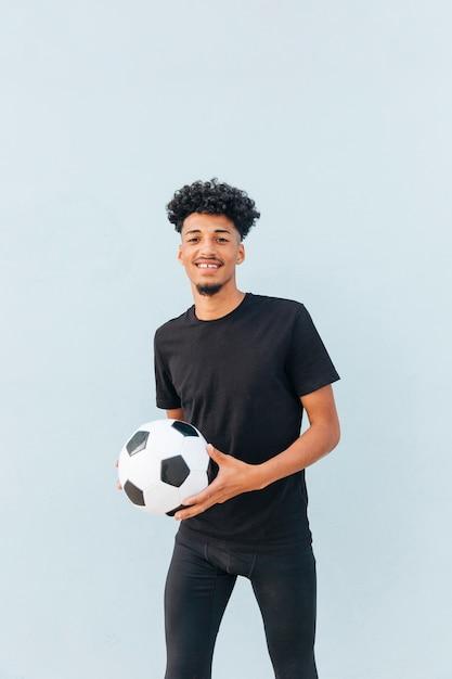 Lächelnder fußballspieler, der ball hält und kamera betrachtet Kostenlose Fotos