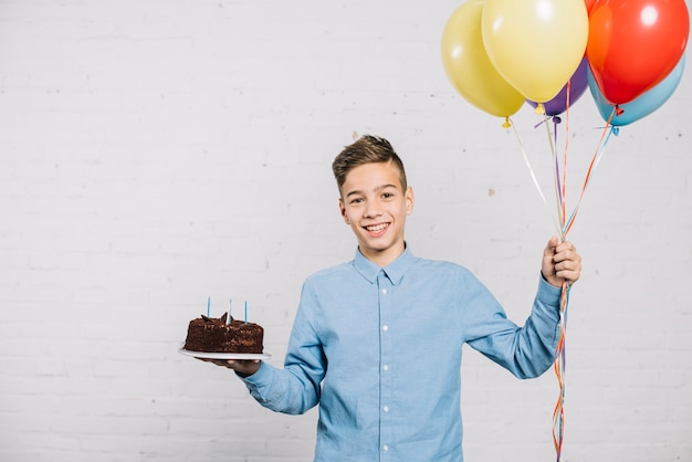 Lächelnder geburtstagsjunge, der die ballone und schokoladenkuchen stehen gegen wand hält Kostenlose Fotos