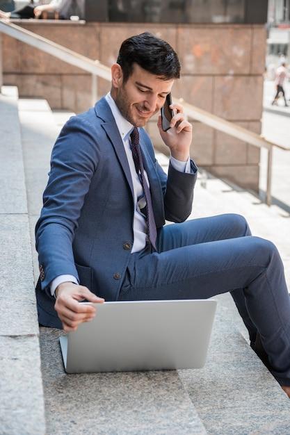 Lächelnder geschäftsmann, der am telefon spricht und laptop durchstöbert Kostenlose Fotos