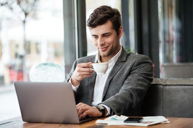 Lächelnder geschäftsmann, der durch die tabelle im café sitzt und laptop-computer verwendet Kostenlose Fotos