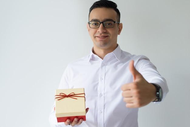 Lächelnder geschäftsmann, der geschenkbox hält und sich daumen zeigt Kostenlose Fotos