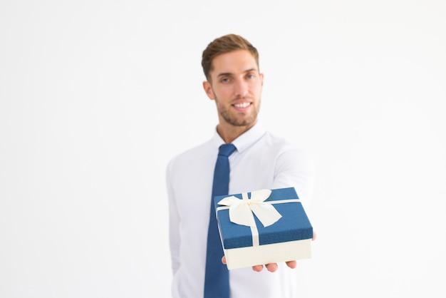 Lächelnder geschäftsmann, der geschenkbox mit band gibt Kostenlose Fotos