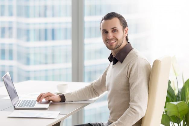 Lächelnder geschäftsmann, der im büro, kamera betrachtend arbeitet, unter verwendung des laptops Kostenlose Fotos