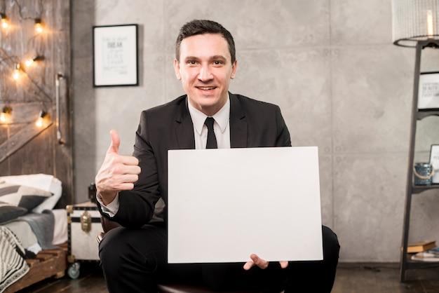 Lächelnder geschäftsmann, der leeres papier hält und oben daumen gestikuliert Kostenlose Fotos