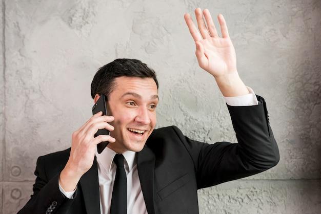 Lächelnder geschäftsmann, der mit der hand wellenartig bewegt und am telefon plaudert Kostenlose Fotos