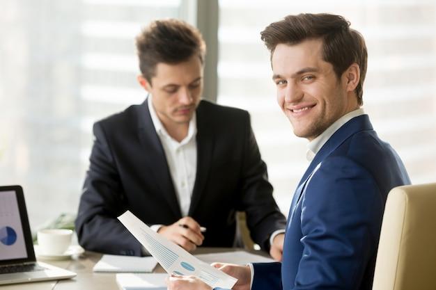 Lächelnder geschäftsmann, finanzanalytiker oder börsenmakler, die a schauen Kostenlose Fotos