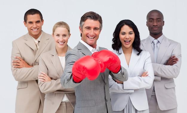 Lächelnder geschäftsmann mit den boxhandschuhen, die sein team führen Premium Fotos