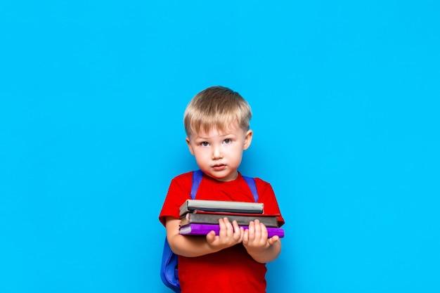 Lächelnder glücklicher netter kluger junge mit rucksack. kind mit einem stapel bücher in seinen händen. fertig für die schule. zurück zur schule Premium Fotos