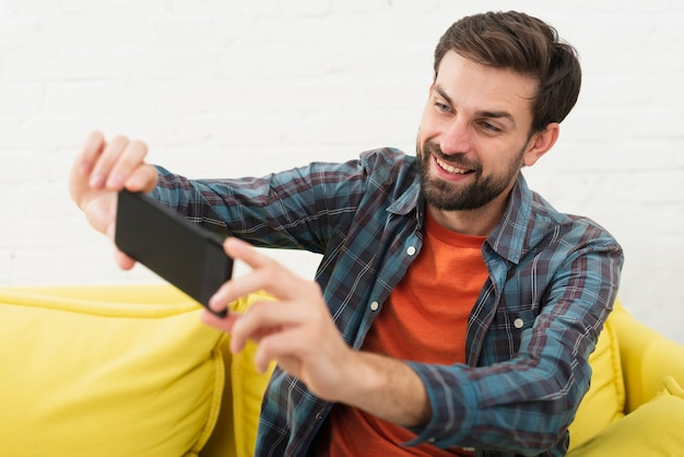Lächelnder gutaussehender mann, der ein selfie nimmt Kostenlose Fotos