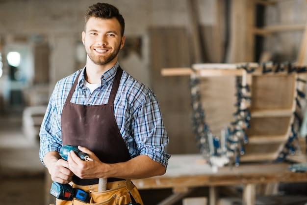 Lächelnder handwerker mit elektrischer bohrmaschine Kostenlose Fotos