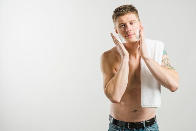 Lächelnder hemdloser junger mann, der schaum auf seiner backe lokalisiert auf grauem hintergrund rasiert zutrifft Kostenlose Fotos